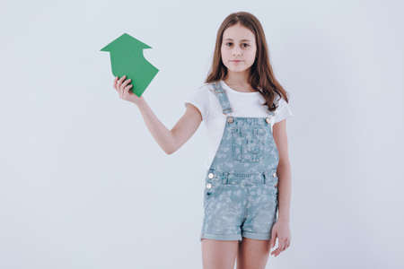 Girl holding a paper arrow as a sign of recycling on white background