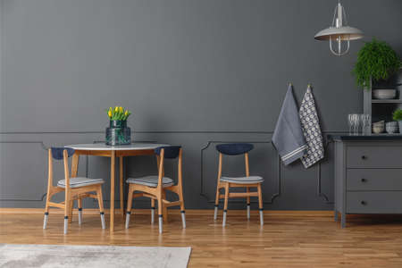 A table and three chairs next to a rug and grey shelves in simple kitchen interior