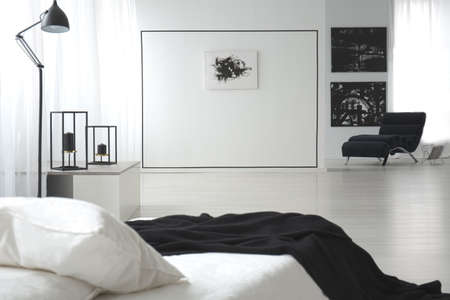 Black and white bedroom interior with double bed, paintings, lamp and wall decoration