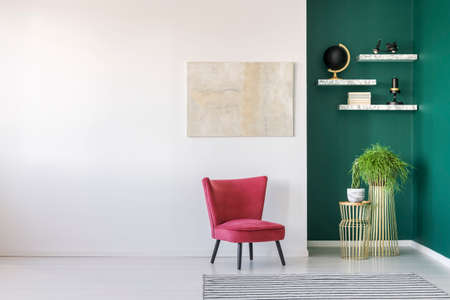 Red chair against white wall with painting in modern living room interior with shelves on green wall