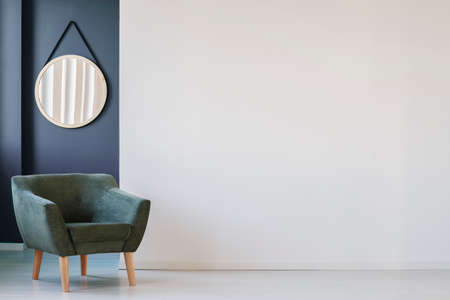 Green armchair against blue wall with round mirror in living room interior with copy space on white wall Banco de Imagens