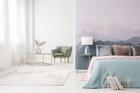 Nowoczesna ława w złotej ramie z eleganckim szklanym wazonem i wygodnym zielonym fotelem w białym wnętrzu pracowni z dużym łóżkiem
