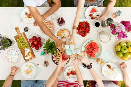 Hohe Winkel von multikulturellen Freunden Toasten an einem Tisch mit gesunden Lebensmitteln für Vegetarier