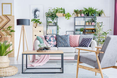 Grey, wooden armchair near table and sofa with patterned, pastel cushions in living room interior