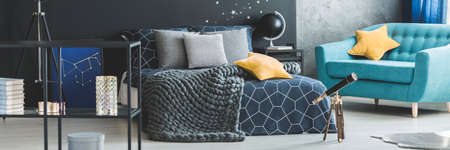 Yellow star pillow on turquoise armchair near telescope in cozy bedroom interior with knit blanket on bed