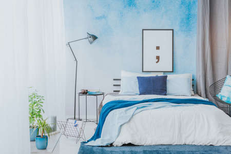 Romantic bedroom interior with blue accents, poster, lamp and watercolor paint on the wall