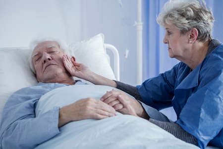 Worried wife stroking the face of her unconscious, terminally ill husband in a hospital Stock Photo