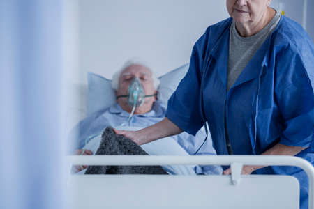 Bedridden man wearing an oxygen mask lying in a hospital with his wife covering his feet with a blanket
