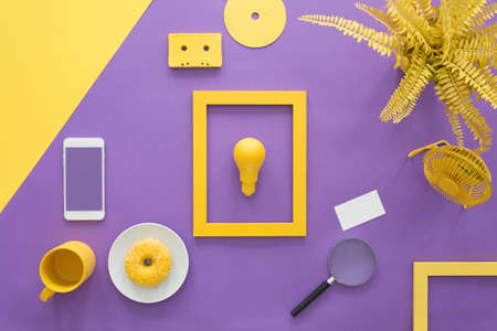 Top view on a primrose yellow bulb in a frame and everyday objects arrangement on an ultra violet work space background