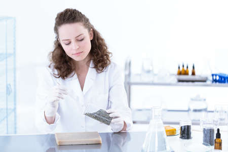 Scientist working with chemical substances in a white lab 版權商用圖片