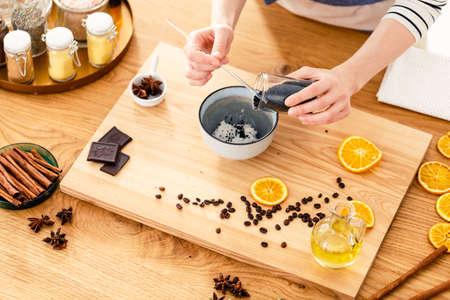 自宅の木箱の上に天然化粧品を準備する女性のクローズアップ 写真素材