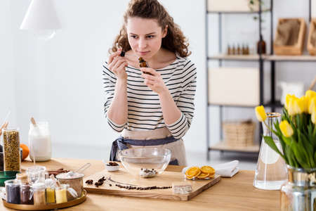 Woman smelling essential oil while preparing organic cosmetics in a kitchen