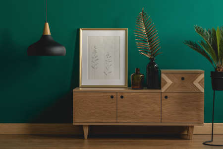 Industrial pendant light next to a stylish dresser and an art poster in a golden frame by a dark green wall of a modern bedroom interior Stock Photo