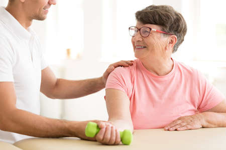 Happy older woman in physical rehabilitation exercising her arm with a hand weight assisted by a physiotherapist Stock Photo