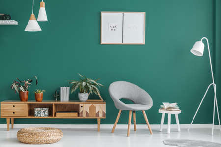 Grey armchair and pouf in green living room interior with wooden cupboard and posters