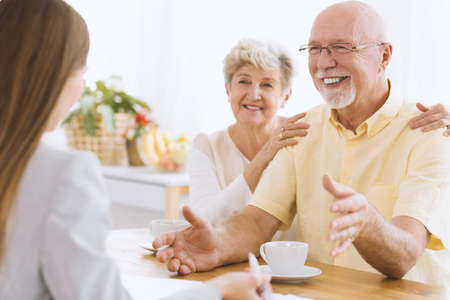 A smiling, elderly couple sitting at a table and talking to an insurance agent