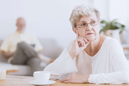 Irritated, elder woman sitting at a table and thinking about her husband