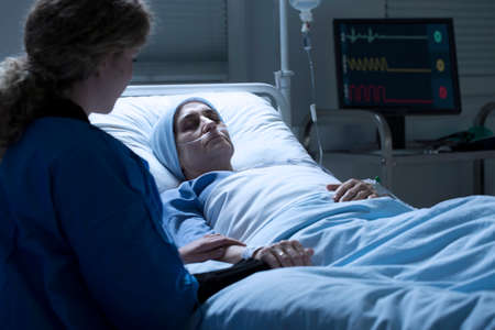 Young woman sitting by a hospital bed and holding the hand of her mother dying of cancer Stock Photo