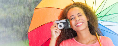 Afroamerican woman taking a picture with analog camera under umbrella