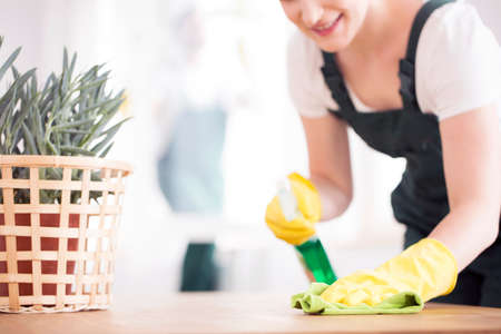 A woman in black overalls and yellow, rubber gloves dusting a table with a plant
