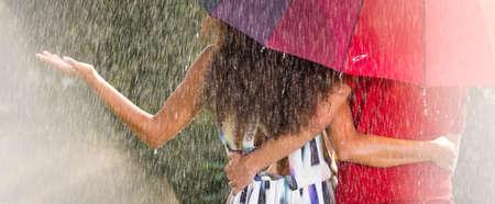 Couple hugging under umbrella during heavy summer rain in the park
