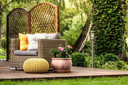 Yellow pouf next to a rattan armchair with grey and gold pillows and pink flowers on wooden veranda Stock fotó