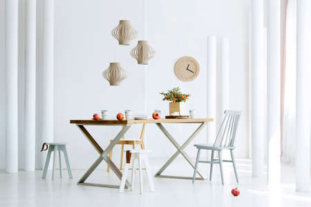 Pomegranates on wooden dining table and floor in dining room interior with a clock on the wall