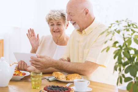 A happy, elder couple sitting at a table in dining room and watching photos on a tablet Zdjęcie Seryjne