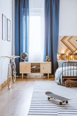 Modern, practical room interior with blue, long curtains, bicycle and striped carpet