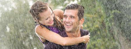 Glimlachende jonge mens die mooi meisje op zijn rug houden tijdens zware de zomerregen