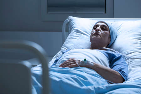 Sick, elderly woman with a headscarf and eyes closed dying alone of cancer in a hospital bed Stock Photo