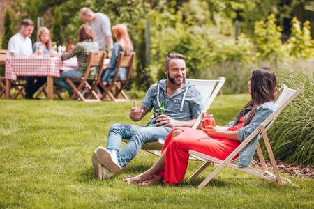 Vrienden ontspannen op ligbedden en bier drinken in de tuin Stockfoto