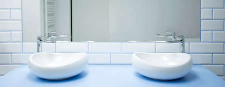 Close-up of two symmetrical washbasins in bright bathroom interior with white tiles and a mirror Stock Photo