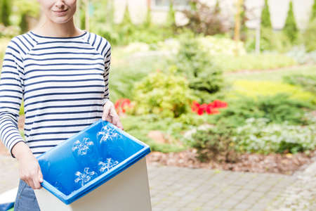 Smiling woman segregating garbage and standing with a wastebasket in the garden