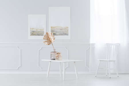 Golden leaf decoration in a vase on a coffee table and a wooden chair in a white elegant living room interior
