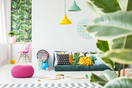 Toys lying around on the floor in bright kids room interior with plants and green sofa