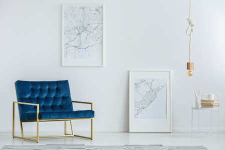 Classy furniture and framed map posters on a white wall in a luxurious, designer living room interior with minimalist decor Banco de Imagens
