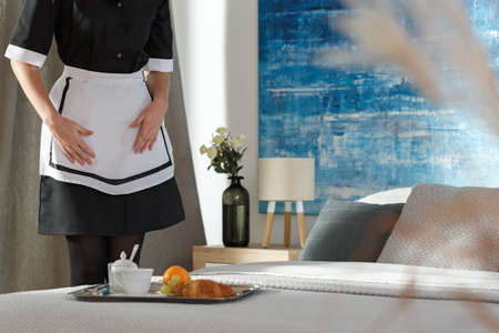 Housemaid in a bedroom putting a tray with breakfast food, on the bed
