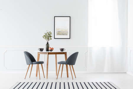 Small dining furniture set and a striped rug in a minimalist white interior with art above the table Foto de archivo