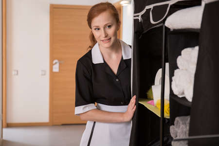 Cleaning lady standing in a hotel corridor with a portable closet Zdjęcie Seryjne - 98996403