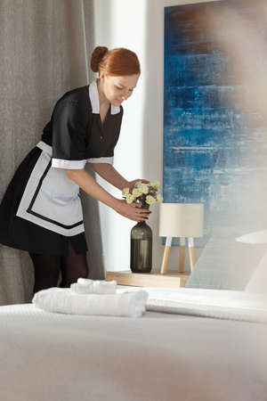 Maid arranging flowers in a hotel room next to a bed during cleaning