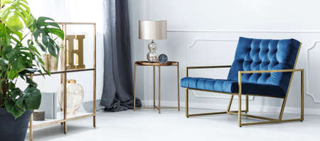Navy blue armchair next to gold table with lamp and clock in sophisticated living room interior Imagens