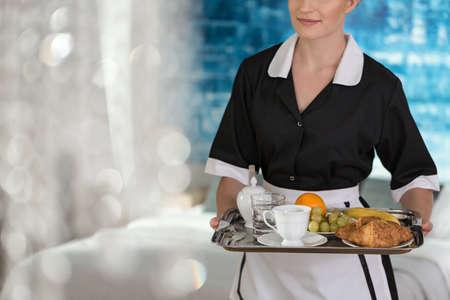 Pokojówka trzymająca tacę z owocami, kawą, wodą i rogalikami dla gościa hotelowego