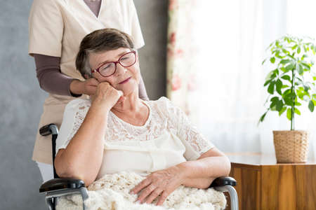 Old woman in a wheelchair with her granddaughter standing behind her Stock Photo
