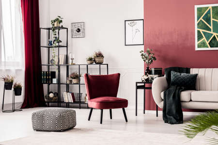 Patterned pouf, red armchair and white sofa in living room interior with burgundy accents Фото со стока