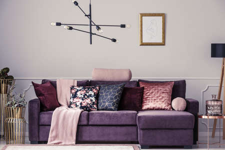 Modern lamp and violet sofa decorated with patterned pillows in a living room interior