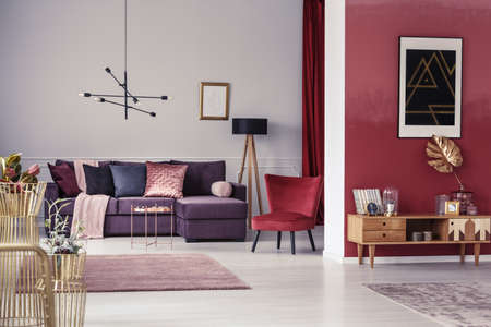 Spacious, maroon apartment interior with corner sofa, red armchair and wooden cupboard