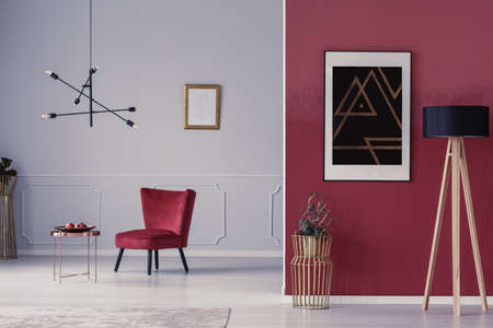 Open space sitting room interior with red armchair, copper coffee table, wooden lamp and painting on the wall