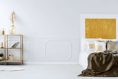 King-size bed, empty wall and golden shelf with decorations in bedroom interior Stock Photo