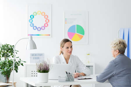 Elderly woman talking to a female doctor at a diet consultation in a bright office Standard-Bild